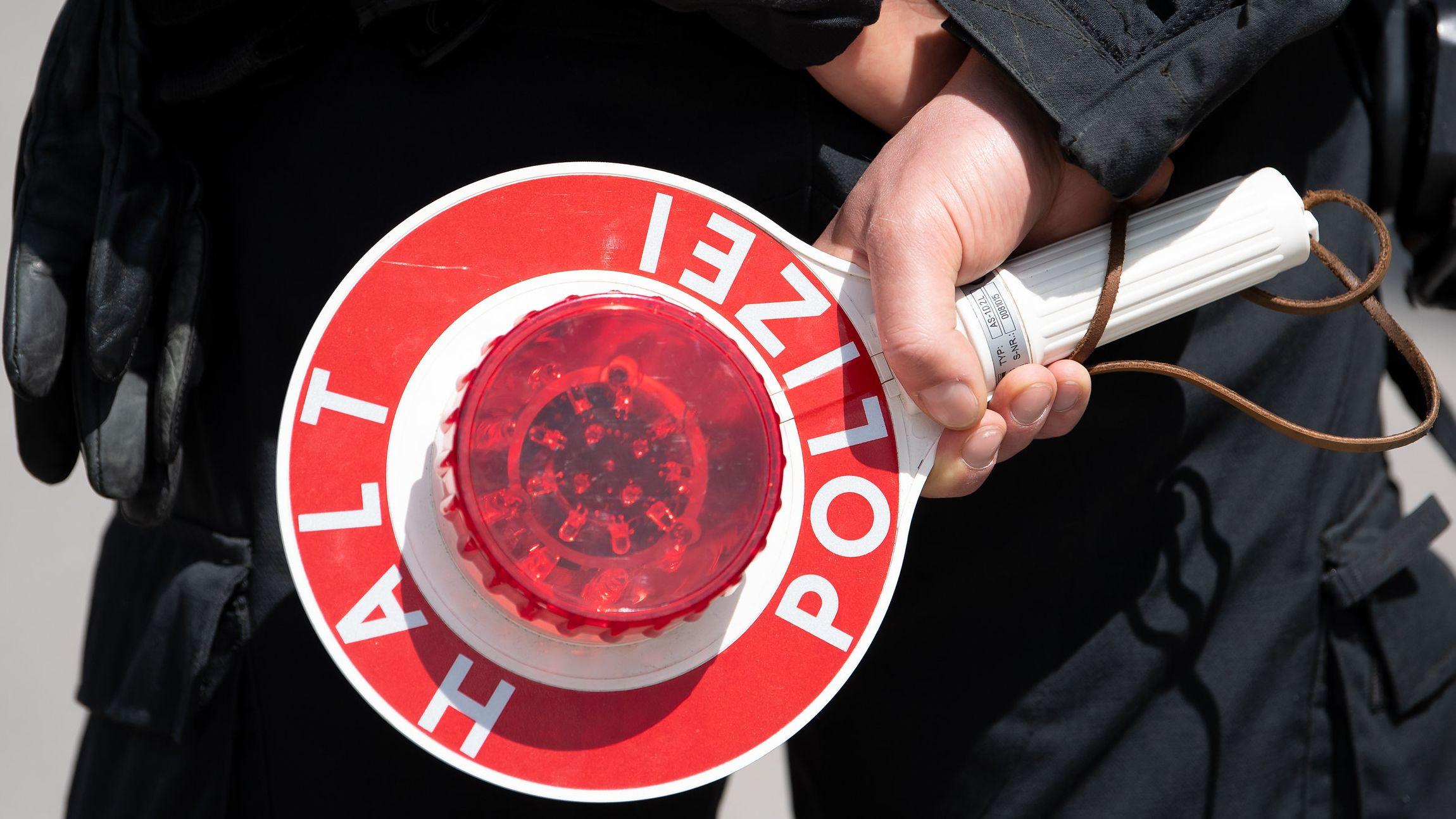 """Polizist hält Kelle mit """"Halt Polizei"""" hinter dem Rücken"""