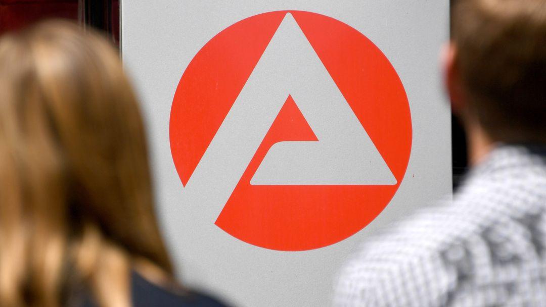 Zwei Personen stehen vor dem Logo der Agentur für Arbeit.