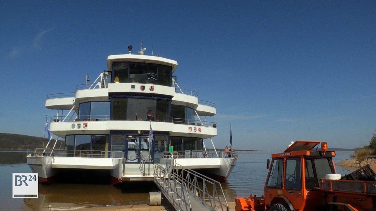 Die MS Brombach liegt im Wasser des Sees, ein Steg führt vom Ufer an Bord.