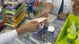Eine Kundin gibt in einer Apotheke ein ärztliches Rezept ab, um verschriebene Medikamente zu erhalten. | Bild:dpa/Arno Burgi