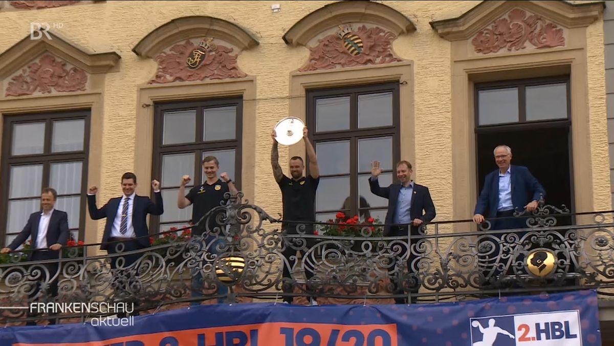 Coburger Handballer stehen auf einem Balkon und halten die Meisterschale in die Höhe.
