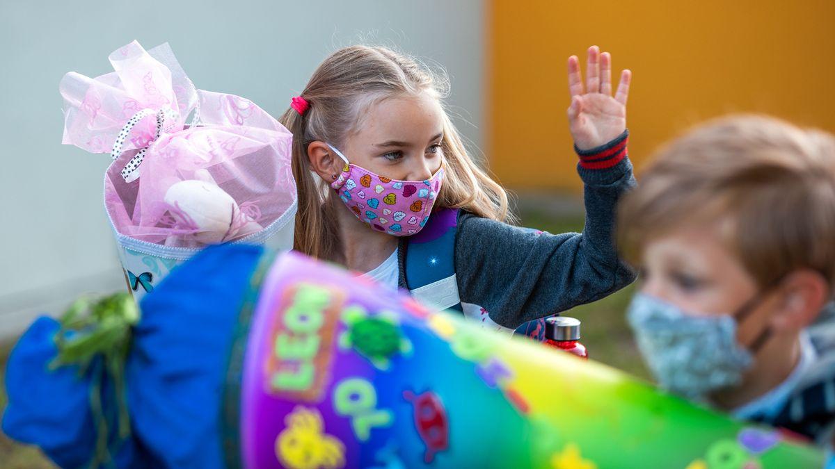 Ein Mädchen mit einer Schutzmaske winkt am ersten Schultag nach den Sommerferien auf dem Weg in ihren Klassenraum