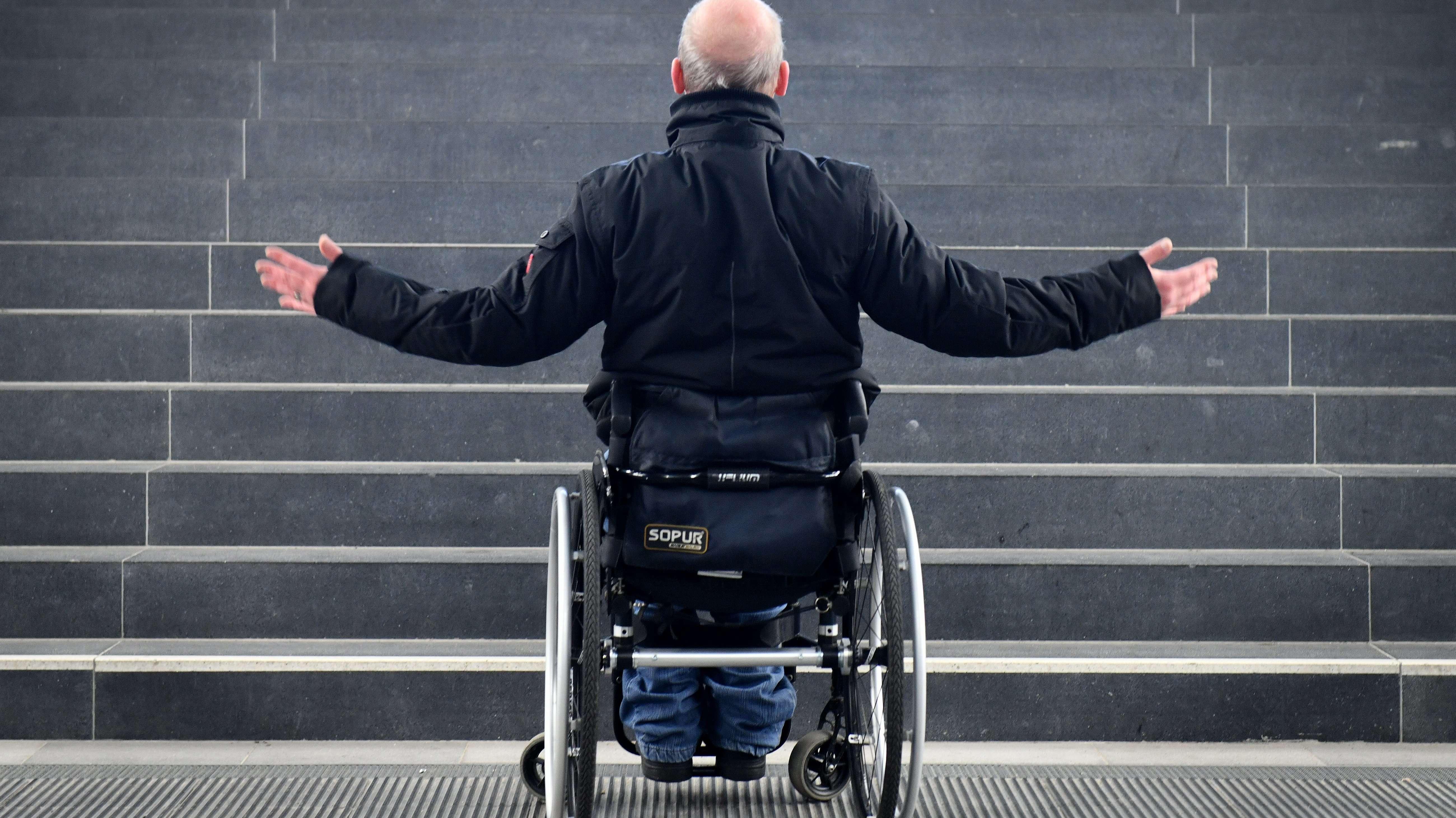 Ein Rollstuhlfahrer steht fassungslos vor einer Treppe