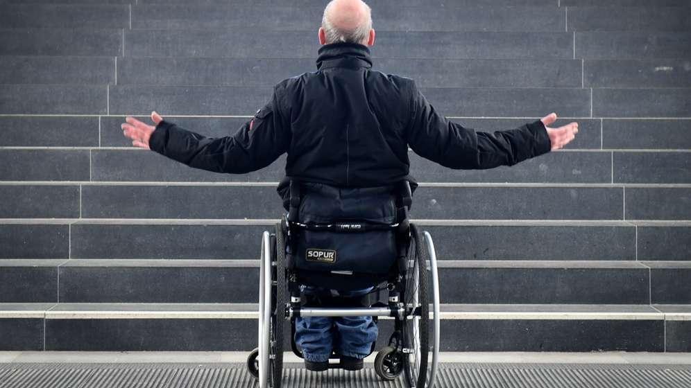 Ein Rollstuhlfahrer steht fassungslos vor einer Treppe   Bild:picture alliance