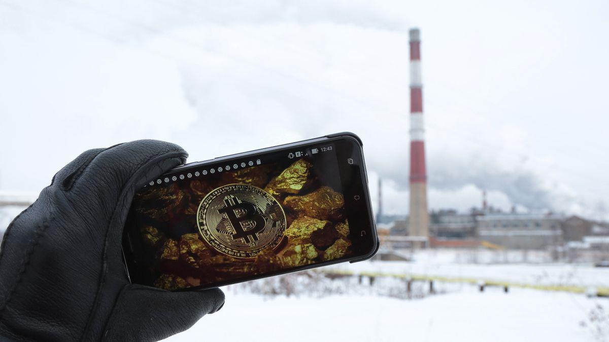Display mit Bitcoin-Logo vor Kraftwerk