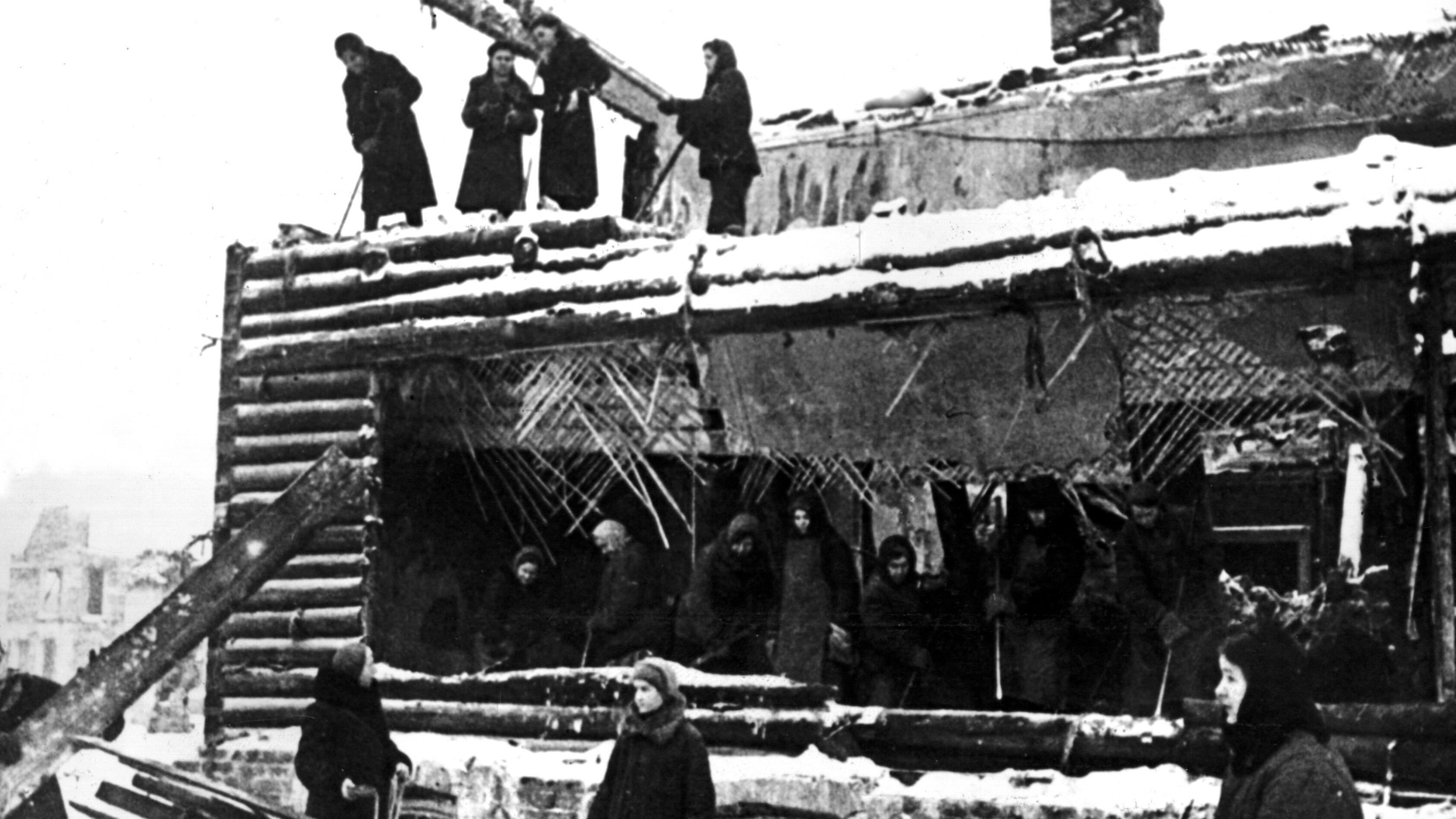 Blockade von Leningrad: Frauen sammeln in zerstörten Holzhäusern Brennholz