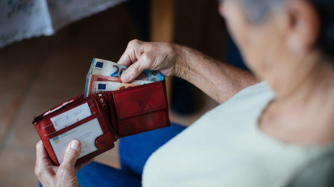 Eine Seniorin mit einem Geldbeutel in der Hand.