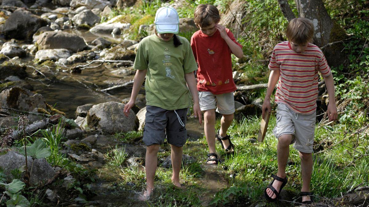 Spielende Kinder an einem Bachbett (Symbolbild)