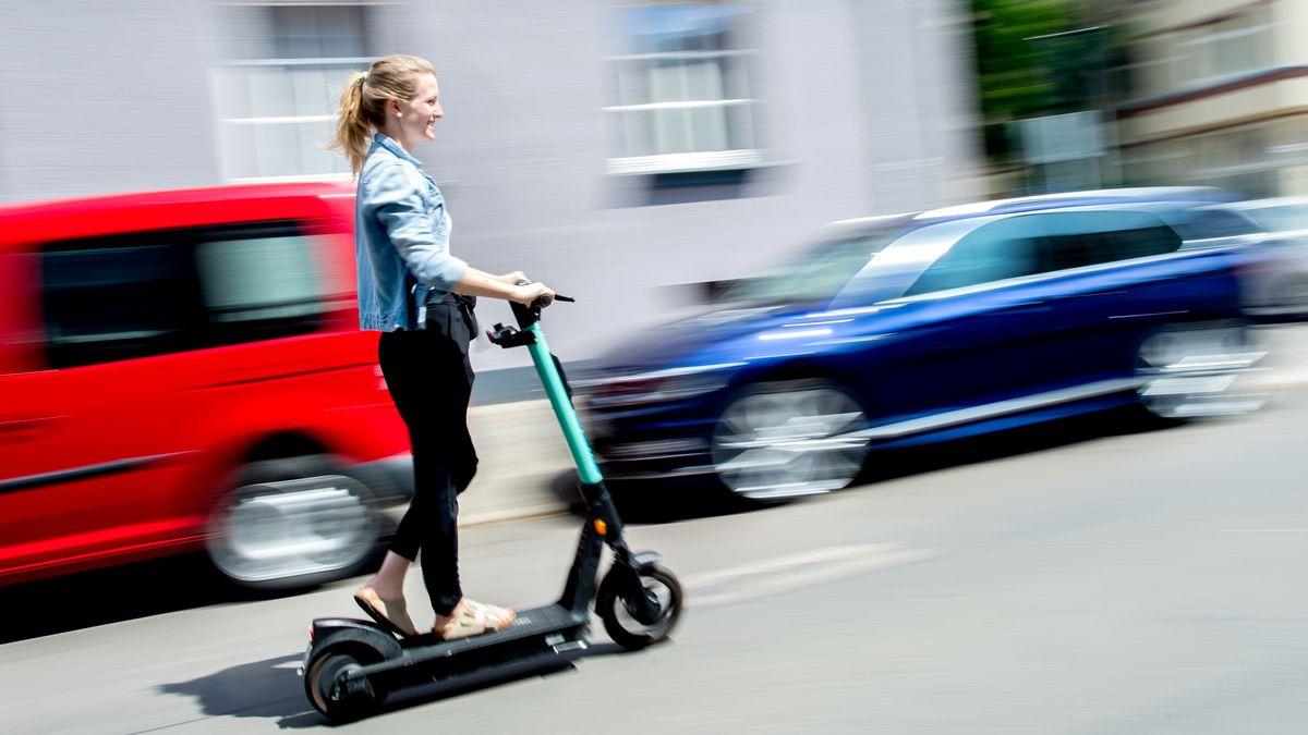 Junge Frau fährt auf einem E-Scooter auf der Straße.