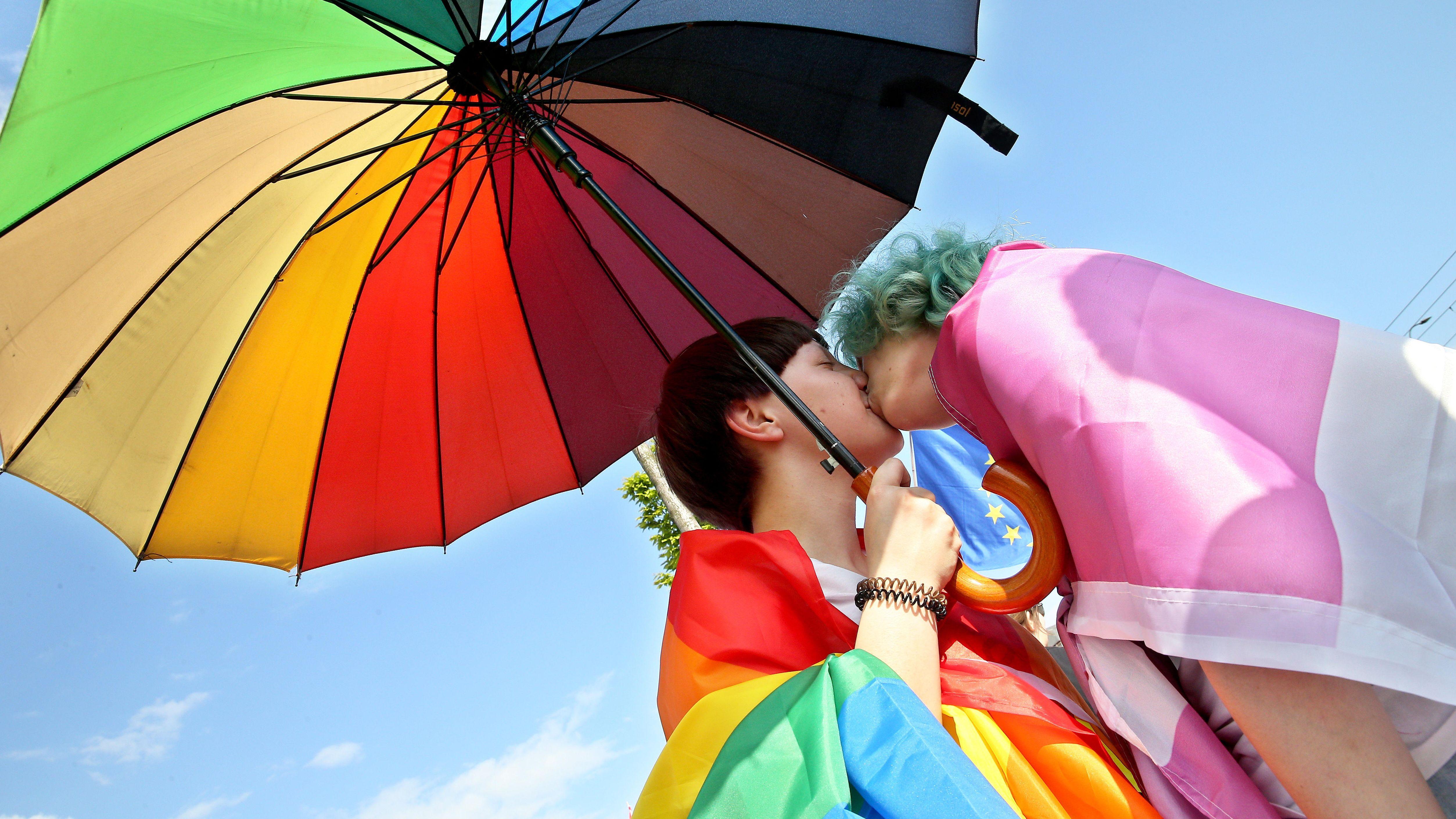 Zwei Frauen küssen sich unter einem Regenbogenschirm.