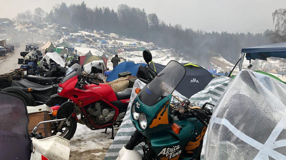 Ein Motorrad am anderen, dahinter Zelte am Hügel