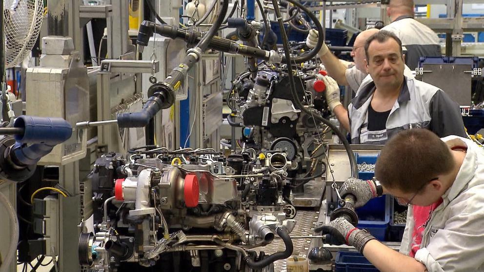 Menschen an Maschinen bei der Autoproduktion.   Bild:BR 2018