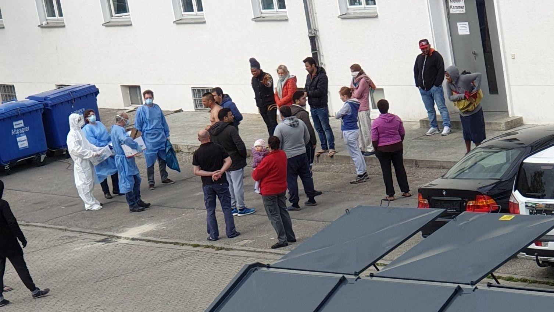 Ärzte in Schutzanzügen stehen vor der Landshuter Asyl-Unterkunft Bewohnern gegenüber
