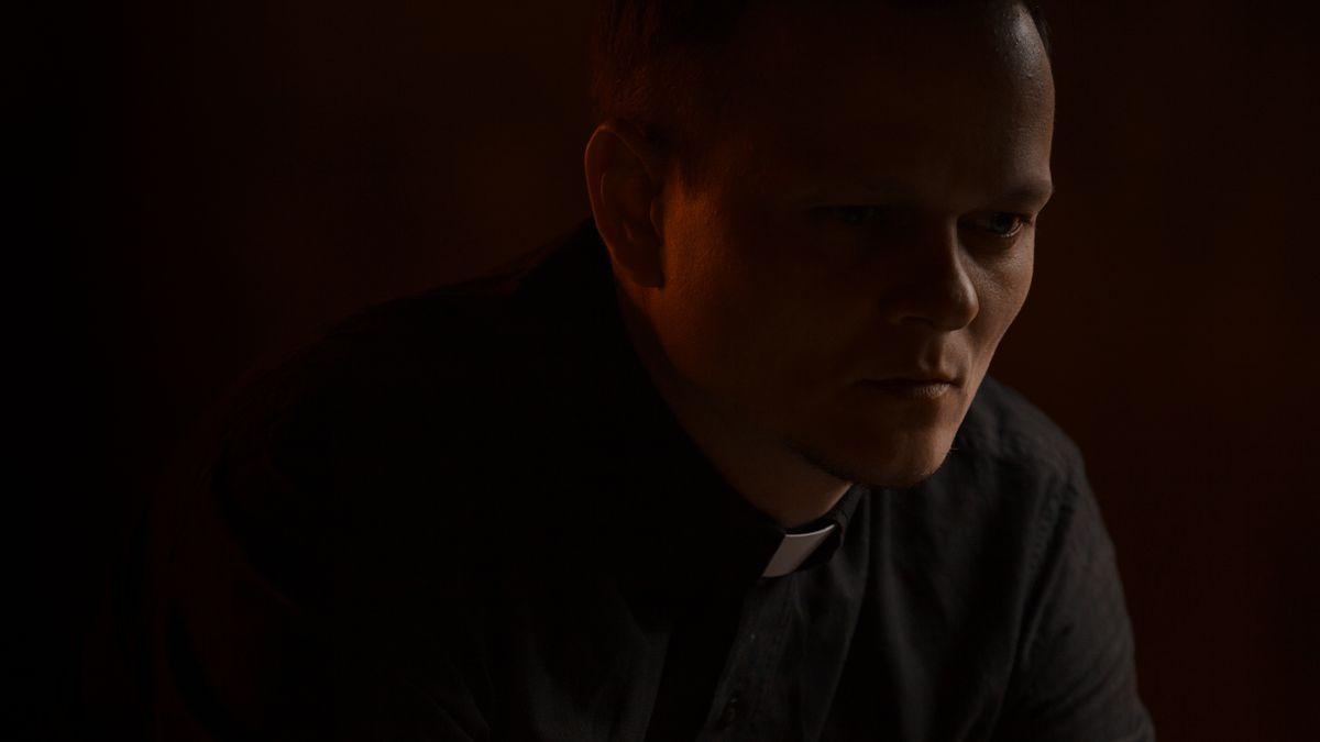 Priester in dunklem Raum.