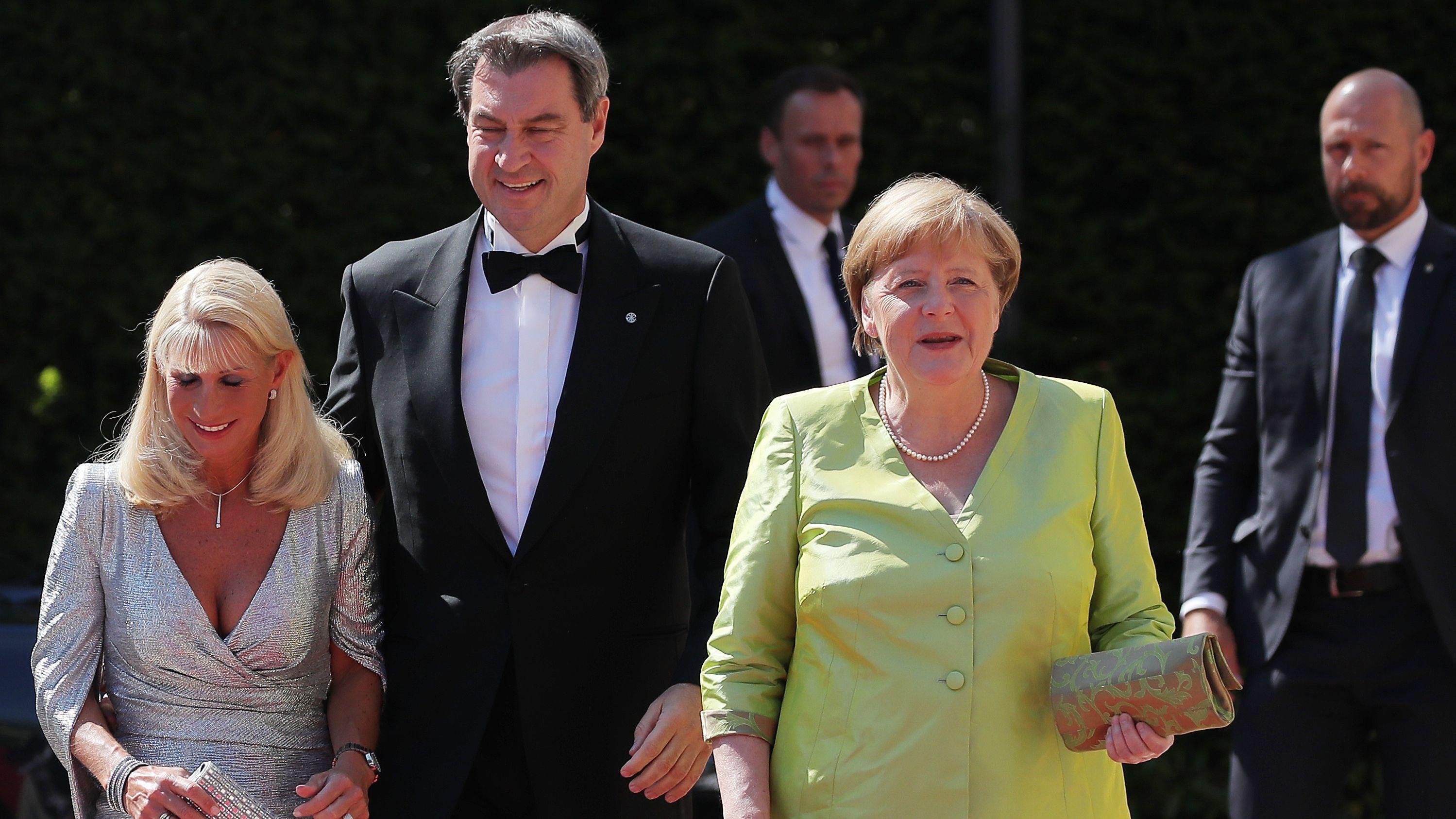 Bundeskanzlerin Angela Merkel, Bayerns Ministerpräsident Markus Söder und seine Ehefrau laufen über den roten Teppich vor dem Bayreuther Festspielhaus.