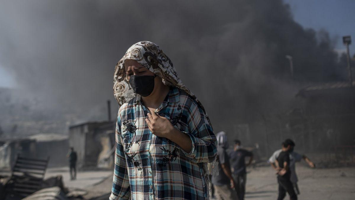 Eine Frau mit Mund- und Kopfbedeckung vor einer große Rauchwolke über dem Flüchtlingslager Moria.
