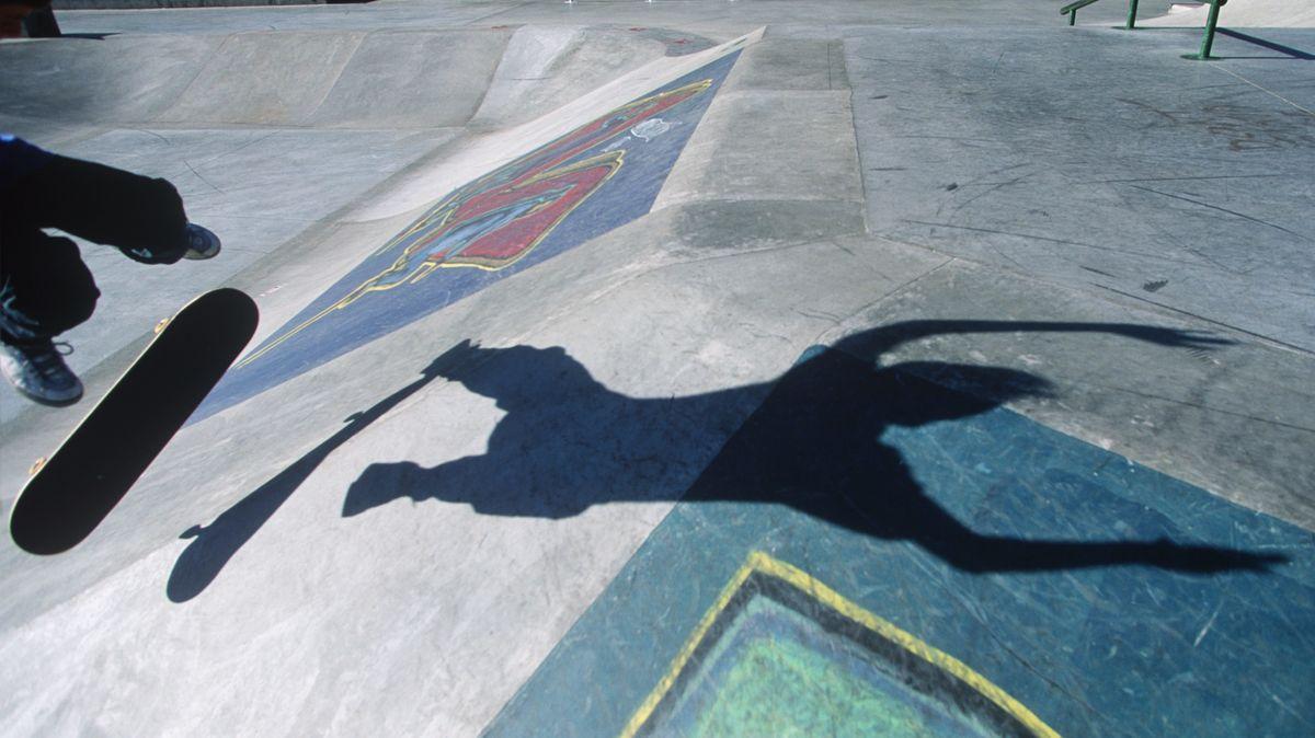 Ein Skateboardfahrer und sein Schatten in einem Skaterpark