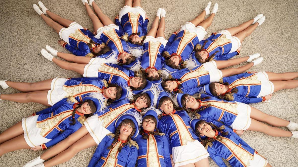 Mitglieder eine Tanzgarde in Uniform liegen im Kreis auf dem Boden