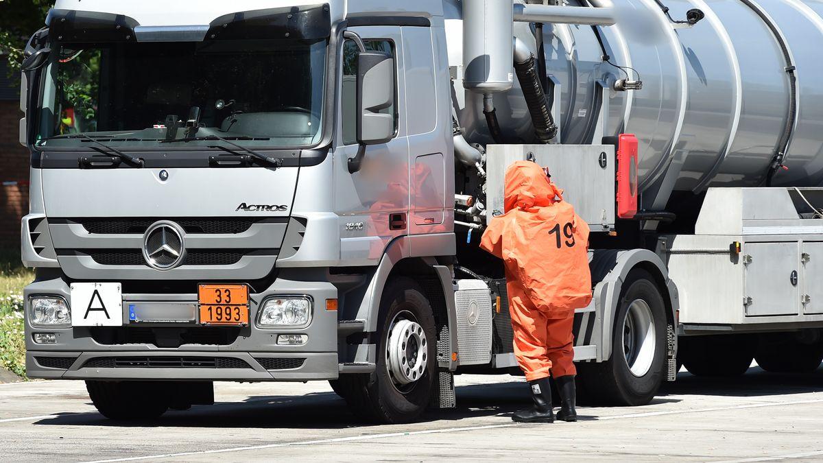 Feuerwehrmann in ABC Schutzanzug kontrolliert einen Gefahrguttransporter (Symbolbild)