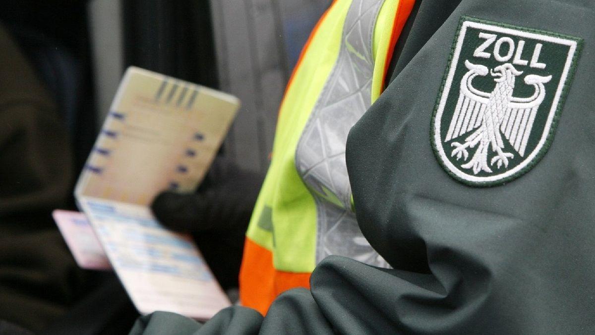 Ein Mitarbeiter des Zolls mit dem Bundesadler auf der Uniform blickt in Ausweispapiere