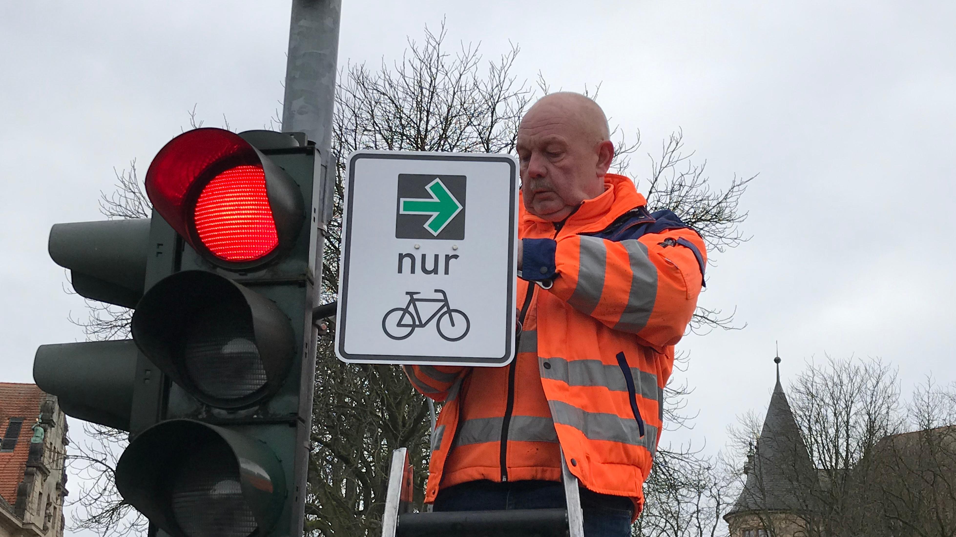 Ein Mann mit neon-orangener Jacke bringt an einer Verkehrsampel ein Schild an. Darauf zu sehen: Ein grüner Pfeil, der nur für Radfahrer gilt.