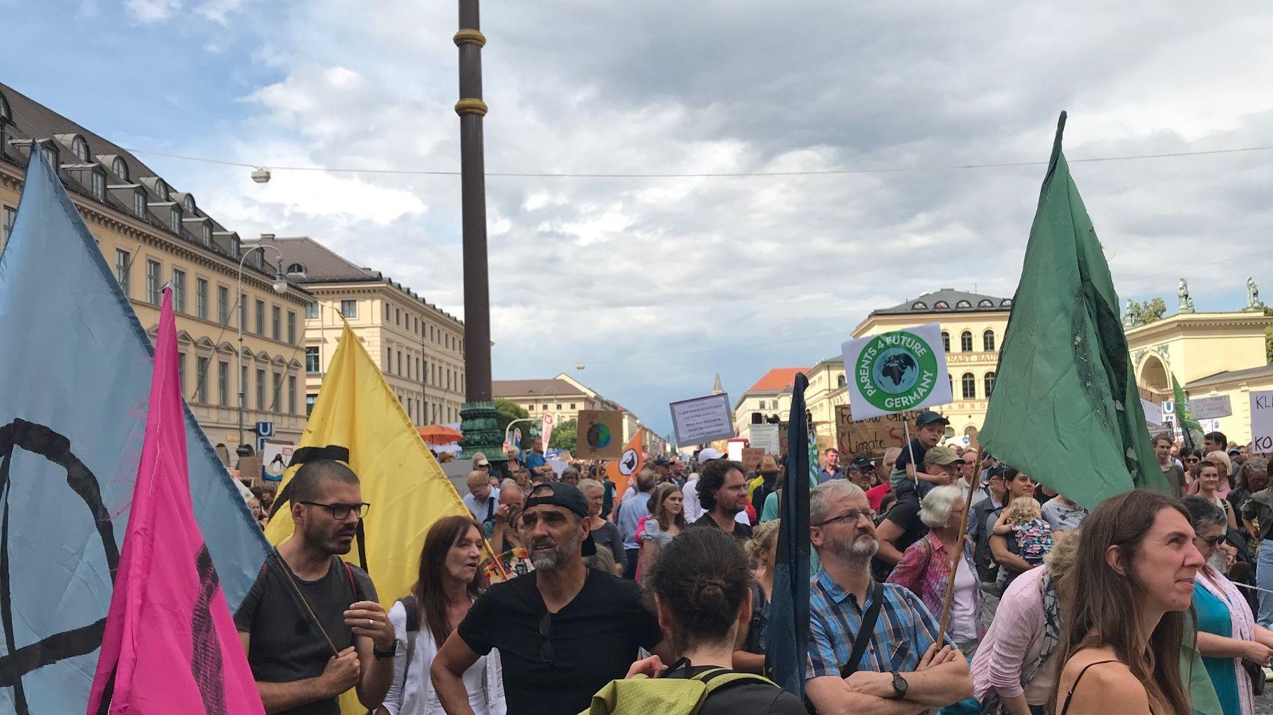 """Demonstrierende bei """"Munich for Future"""" mit Plakaten und Fahnen unter wolkenverhangenem Himmel"""