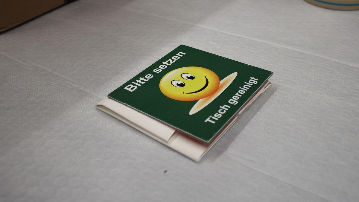 """Ein quadratisches Plastikschild mit grüner Oberfläche und einem lächelnden Emoticon, darüber und darunter in weißer Schrift: """"Bitte setzen. Tisch gereinigt."""""""