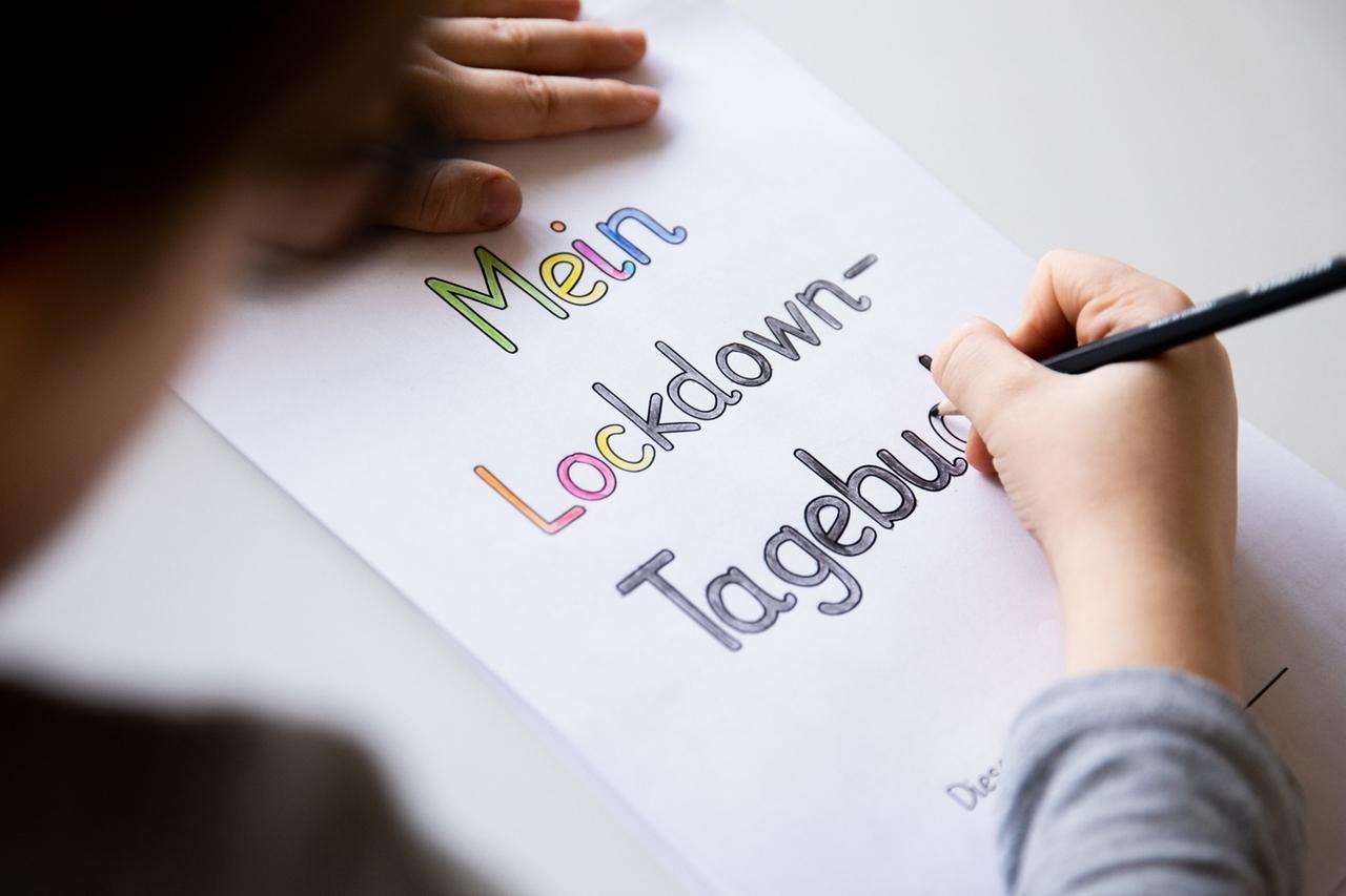 ARCHIV - 14.01.2021, Nordrhein-Westfalen, Haltern am See: Ein Grundschüler malt an einem Tisch im Wohnzimmer die Buchstaben eines Lockdown Tagebuchs aus. Ein Jahr nach dem ersten Lockdown zeichnen sich nach Unicef-Angaben massive Auswirkungen der Corona-Pandemie auf Kinder und Jugendliche ab. Dies ergab der am 20.04.2021 veröffentlichte Unicef-Bericht zur Lage der Kinder in Deutschland 2021. Foto: Rolf Vennenbernd/dpa +++ dpa-Bildfunk +++