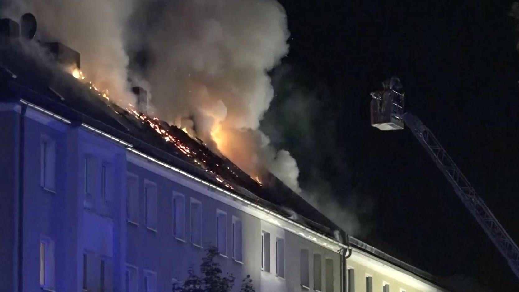 Flammen lodern aus dem Dach eines Mehrfamilienhauses in Hof. Feuerwehrmänner auf Hochleiter löschen.