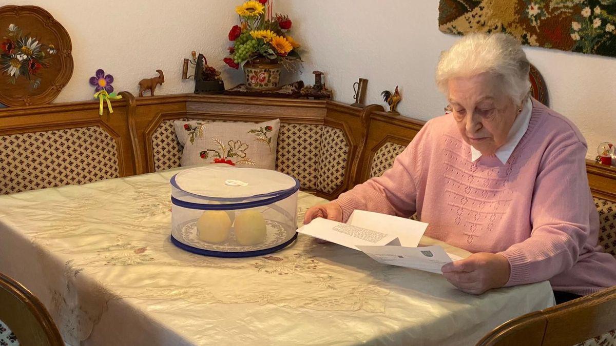 Seniorin mit einem Brief sitzt am Tisch