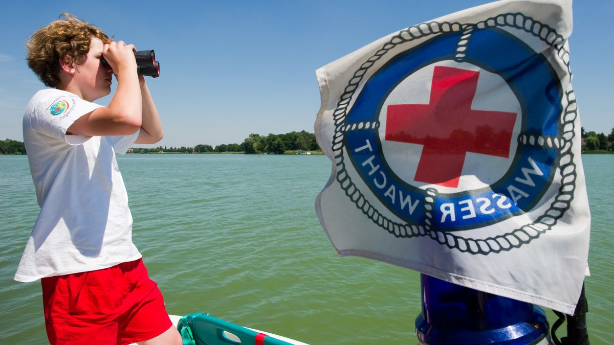 Ein Mitarbeiter der Wasserwacht sucht vom Boot aus einen Badesee mit dem Fernglas ab. (Symbolbild)