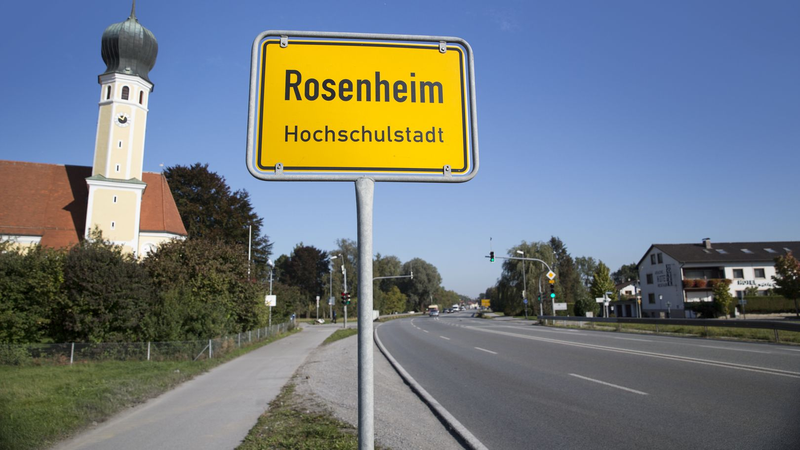 Ortseinfahrt Rosenheim mit Ortsschild, links: Kirche, rechts: Wohnhäuser