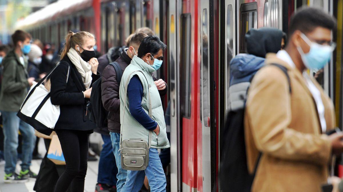 Auf dem Bahnsteig steigen Fahrgäste mit Maske in eine Münchner S-Bahn - alle tragen Masken.