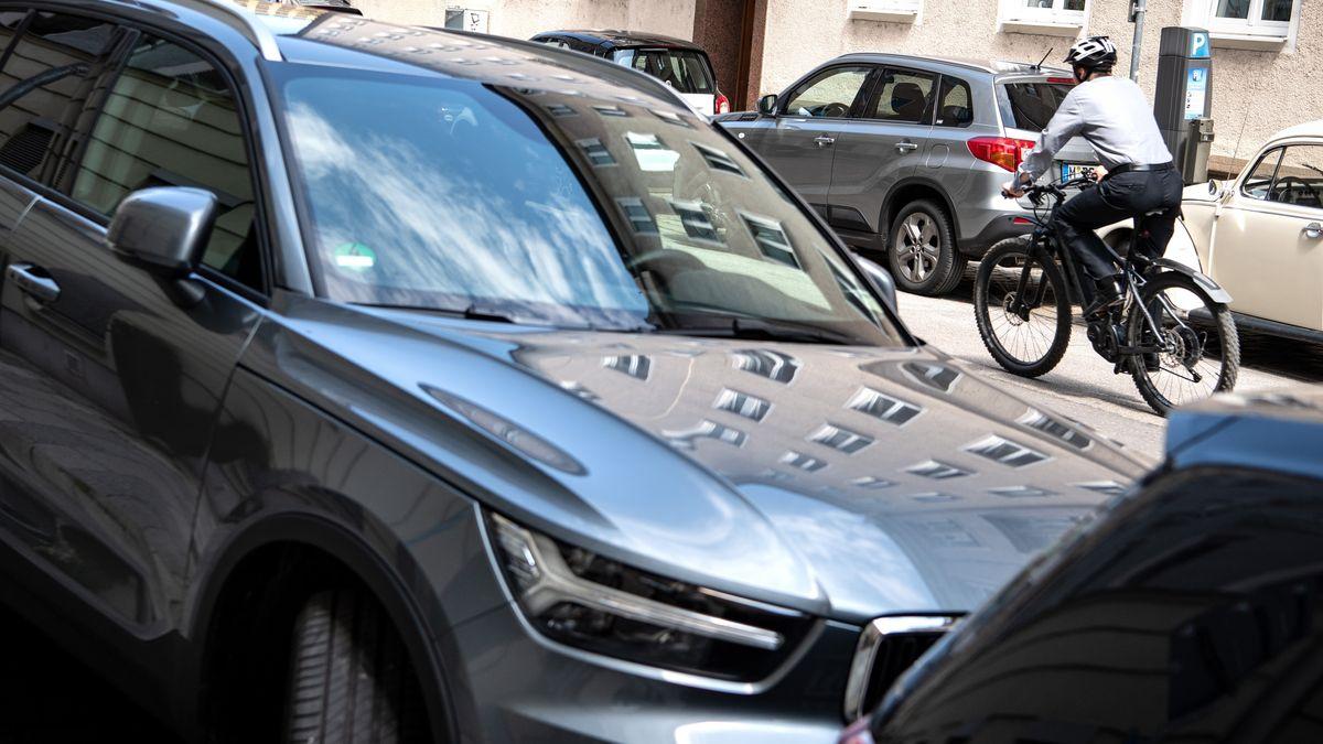 Einsamer Fahrradfahrer auf einer zugeparkten Straße in München
