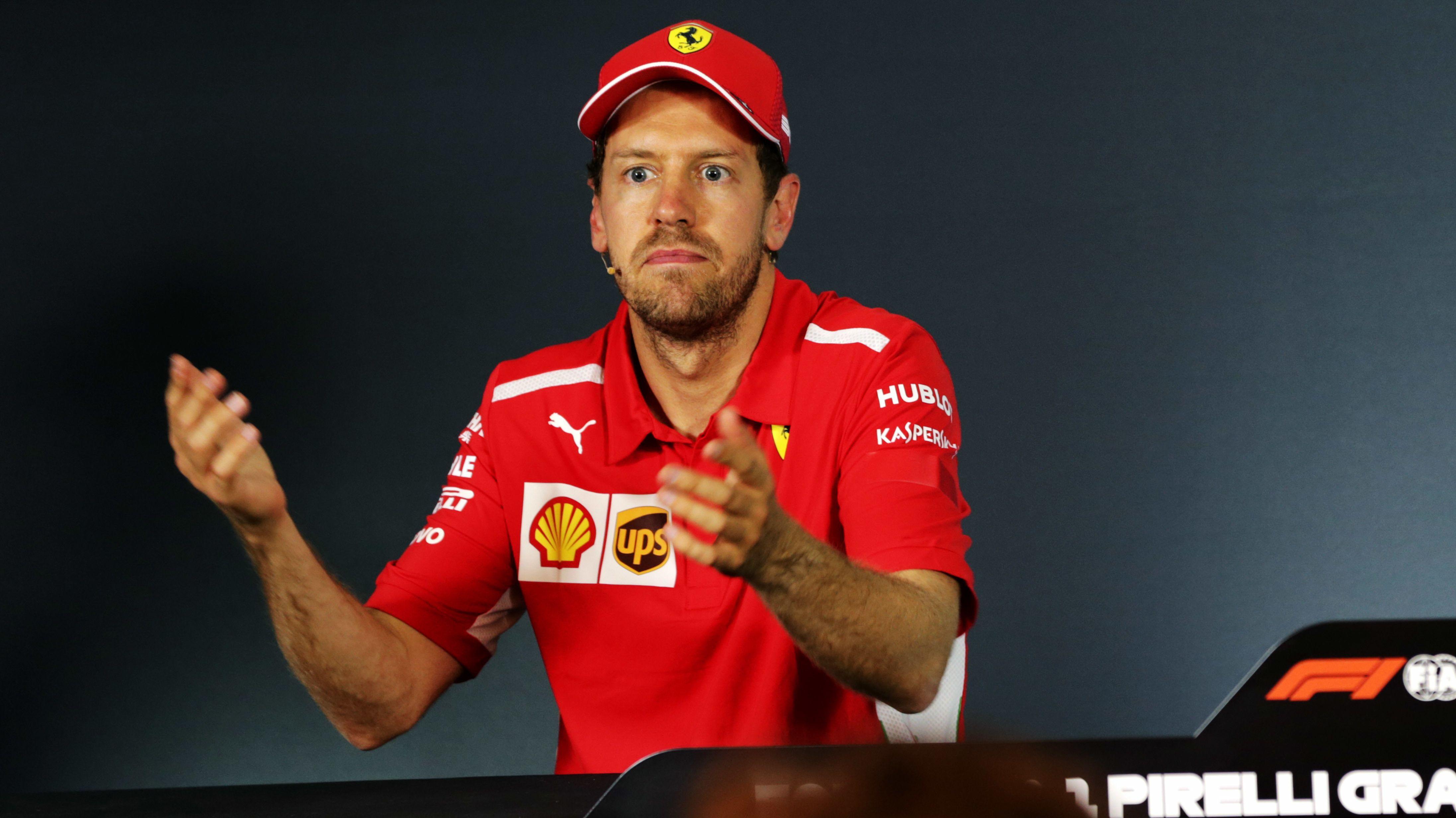 Sebastian Vettel gestikulierend, mit missmutigem Gesichtsausdruck