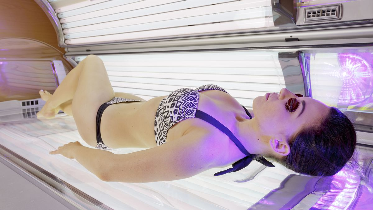Eine junge Frau liegt auf einer Sonnenbank im Solarium.