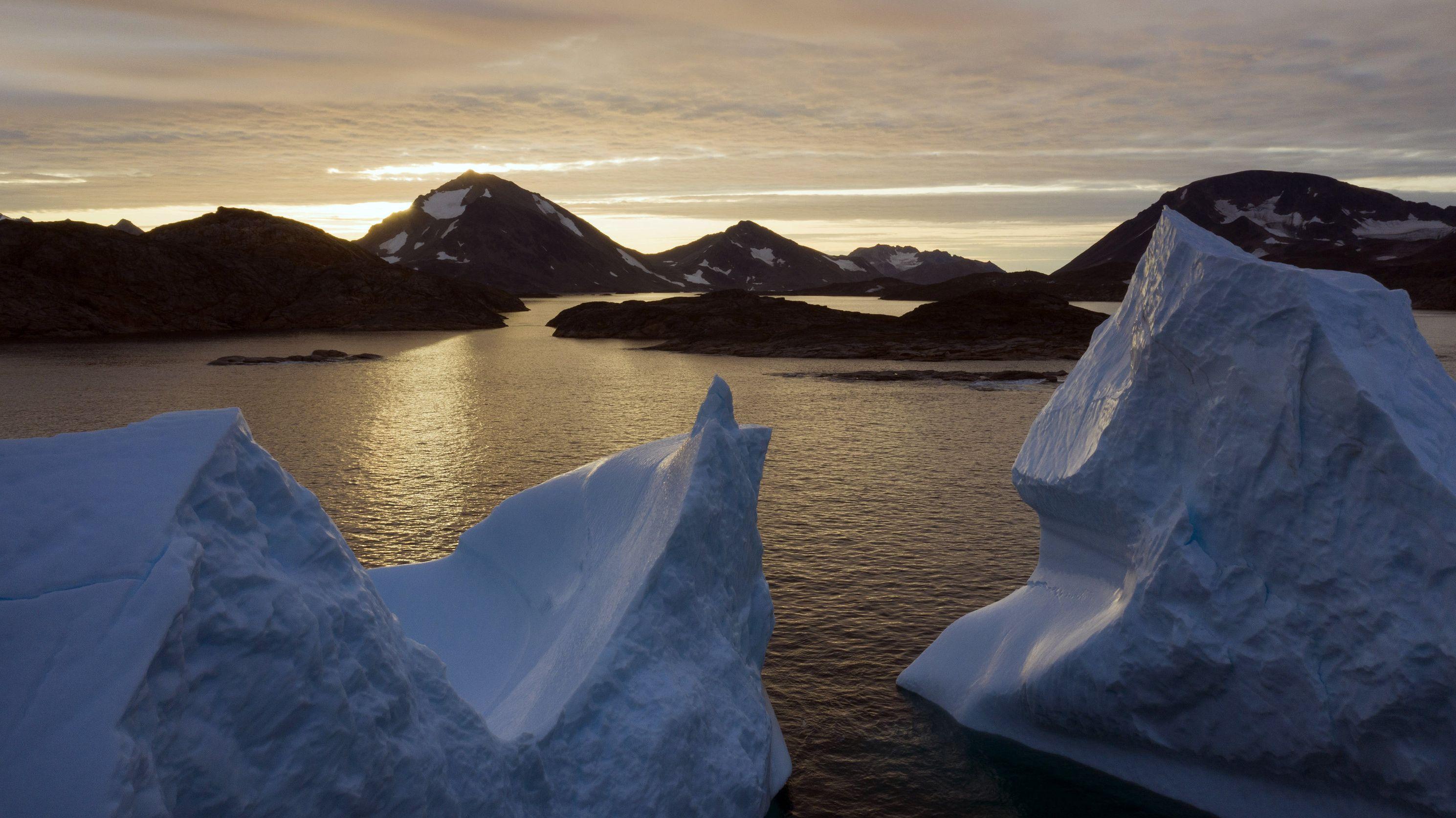 Eisberge treiben bei Sonnenaufgang in der Nähe von Kulusuk, Grönland, auf dem Wasser