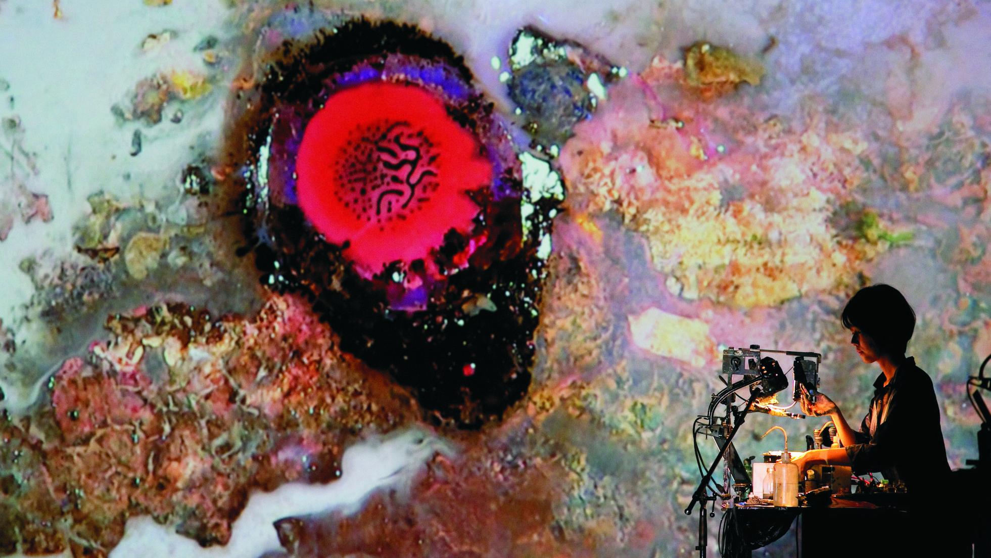 """Künstlerin """"Alive-Painting"""" sitzt beim Lab30-Festival in Augsburg an einem Tisch vor einer Wand mit Farbprojektionen"""