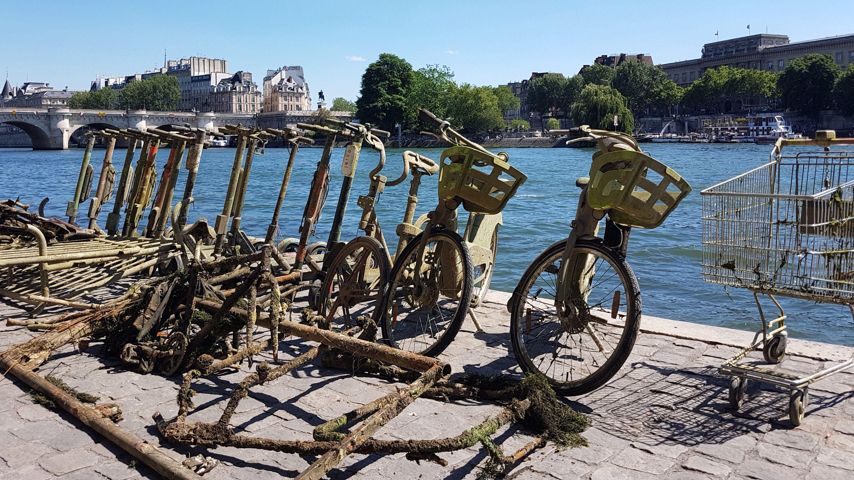 Frankreich, Paris: Aus dem Wasser gefischte Fahrräder, E-Tretroller und ein Einkaufswagen stehen aufgereiht am Ufer der Seine