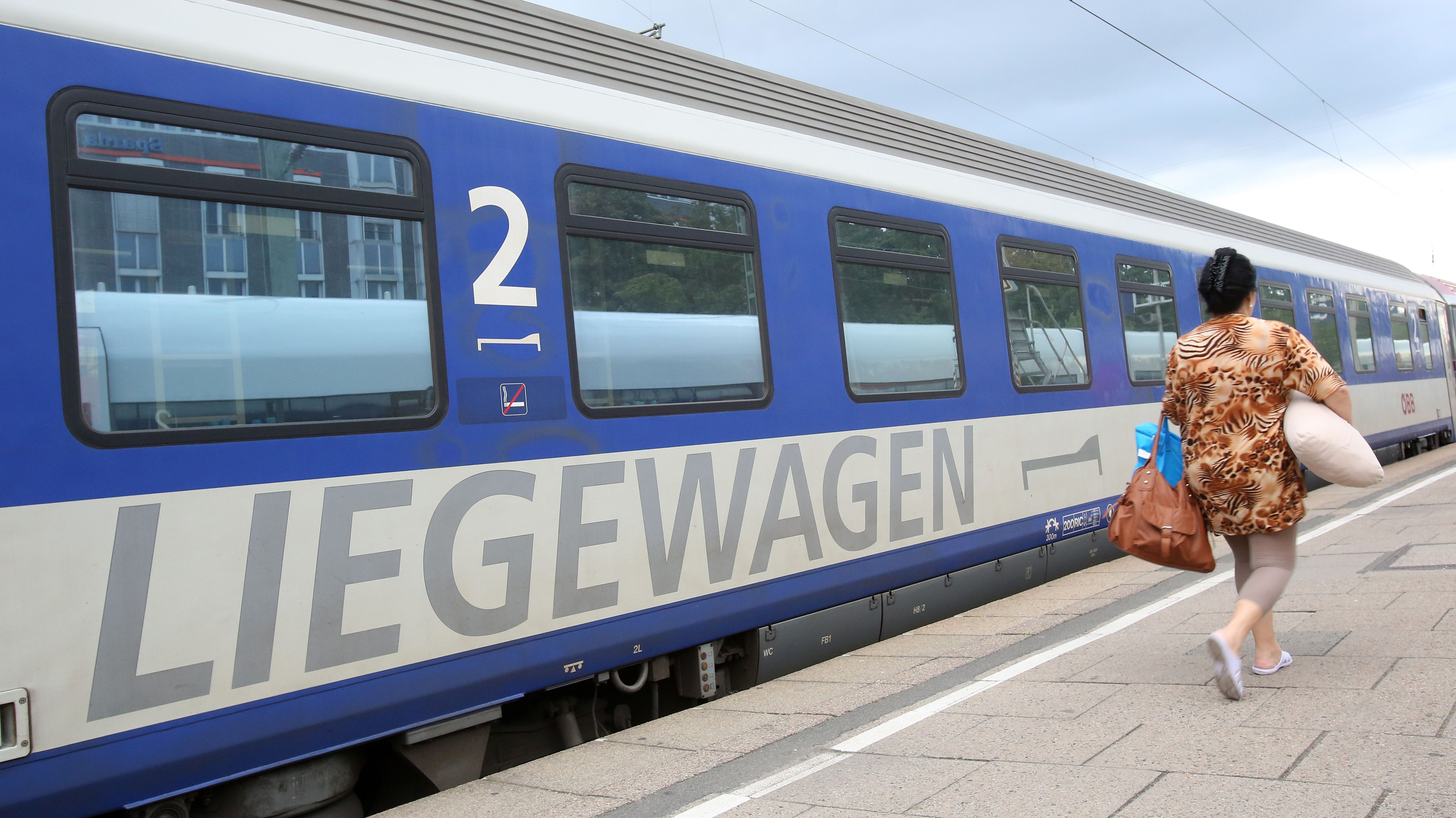 Eine Reisende geht zu einem Nachtzug (EuroNight) der ÖBB.