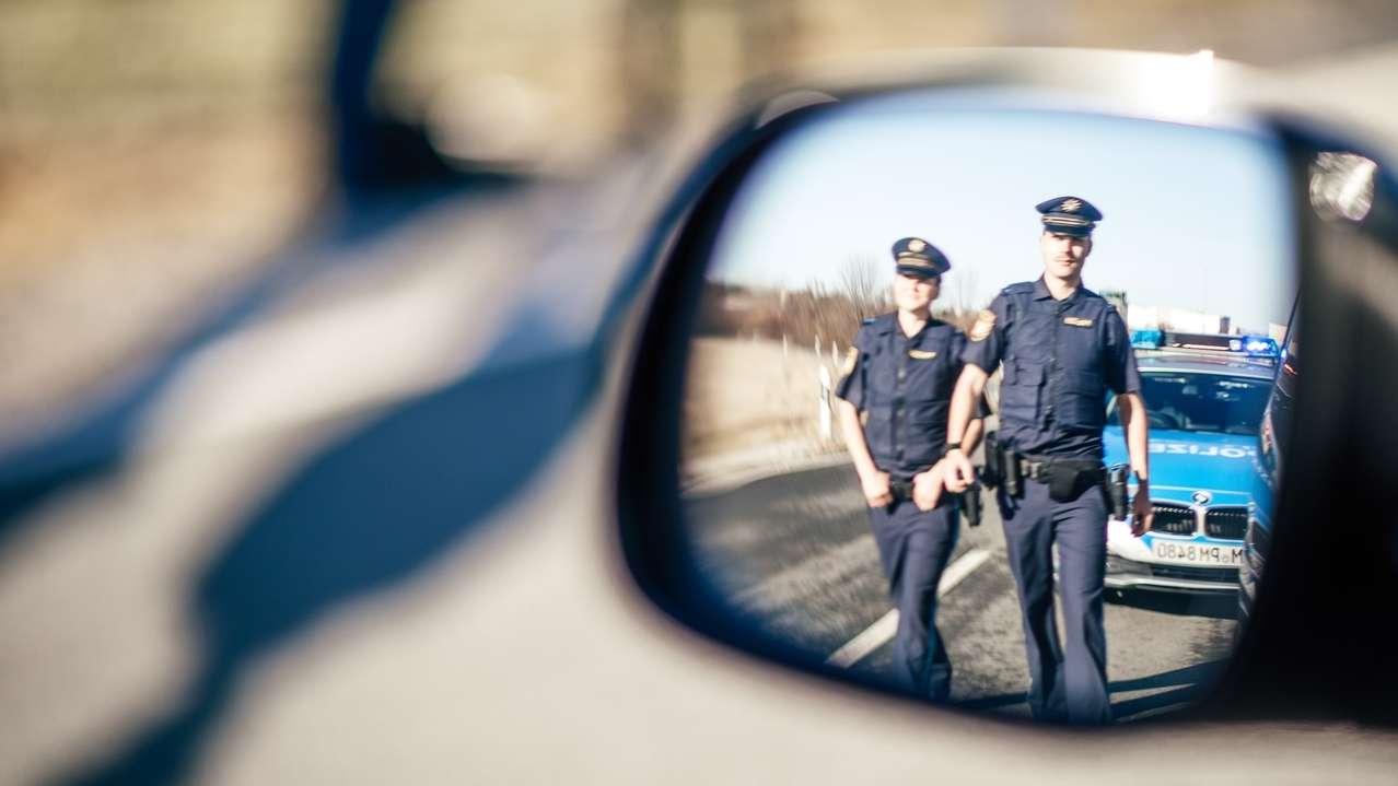 Zwei Polizisten gehen während einer Fahrzeugkontrolle an einer Landstraße auf das Auto zu.