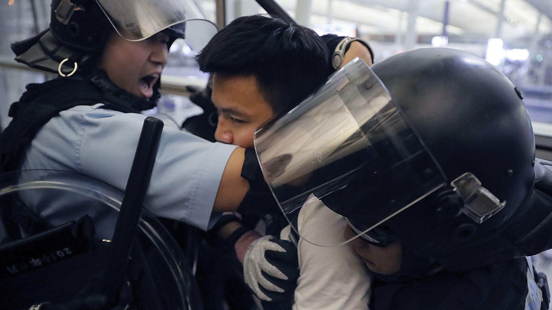 Polizisten in Schutzausrüstung nehmen einen Demonstranten im Hongkonger Flughafen fest.