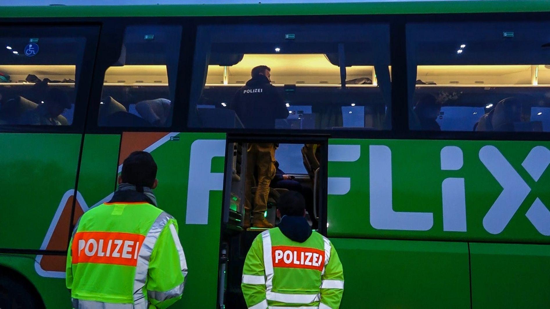 Polizisten kontrollieren einen Fernbus.