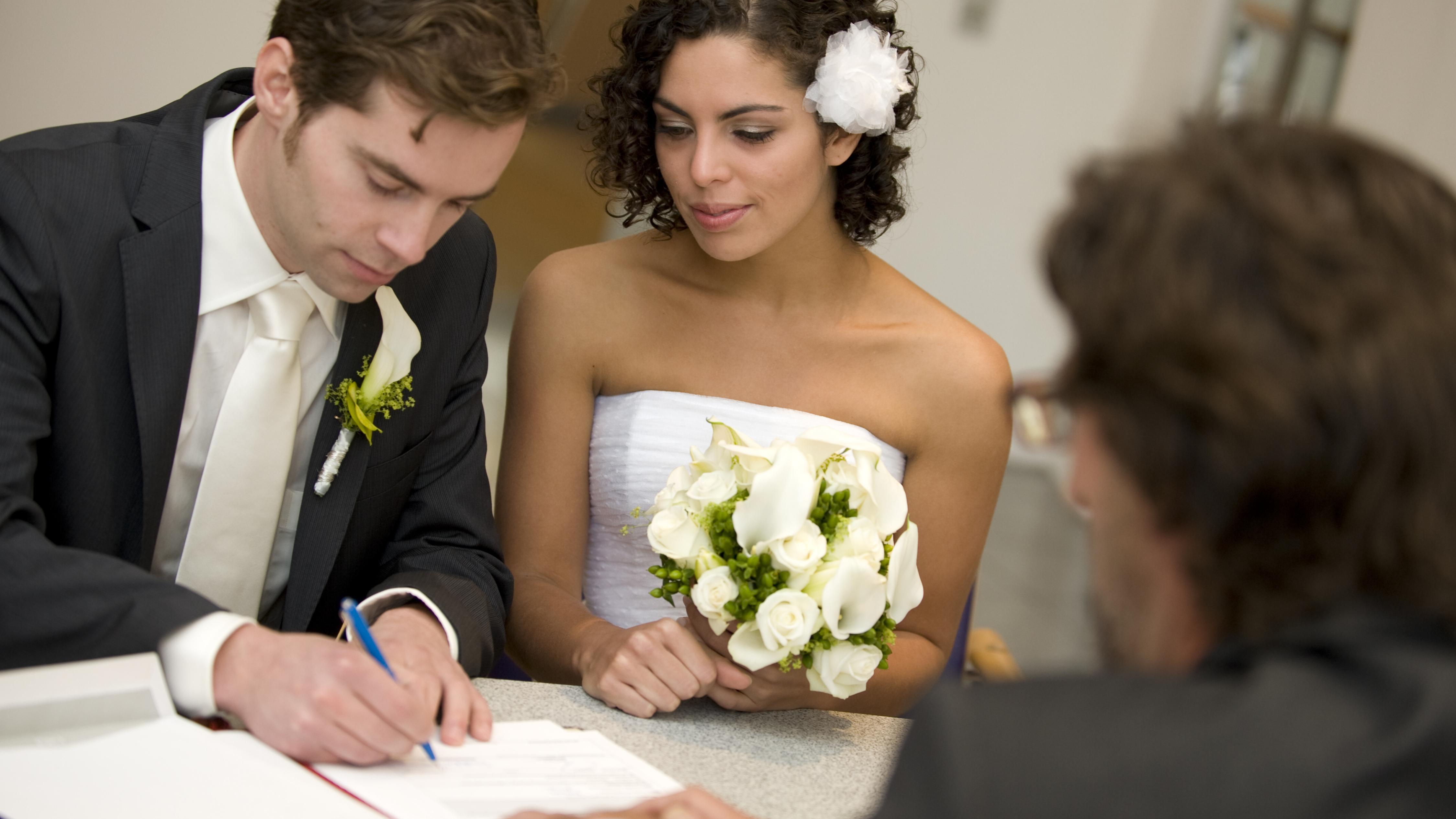 Ein Hochzeitspaar unterschreibt die Heiratsurkunde