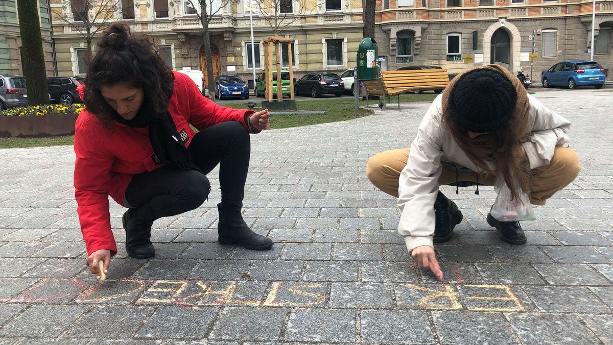 Paula Jorge und Kim Hesterberg gehen zum Adolf-Pichler-Platz, wo die sexualisierte Belästigung stattgefunden hat. Mit bunten Kreiden schreiben sie diese dort auf den Asphalt.