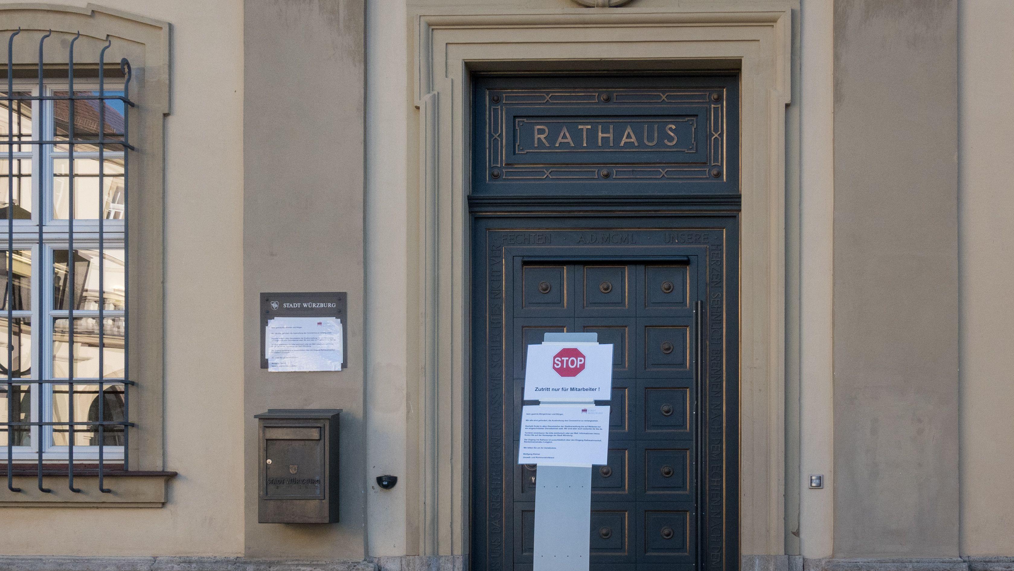 Stop-Schild vor einem geschlossenen Rathaus (Symbolbild).