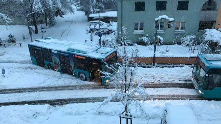 Busse stehen auf schneebedeckten Straßen quer.