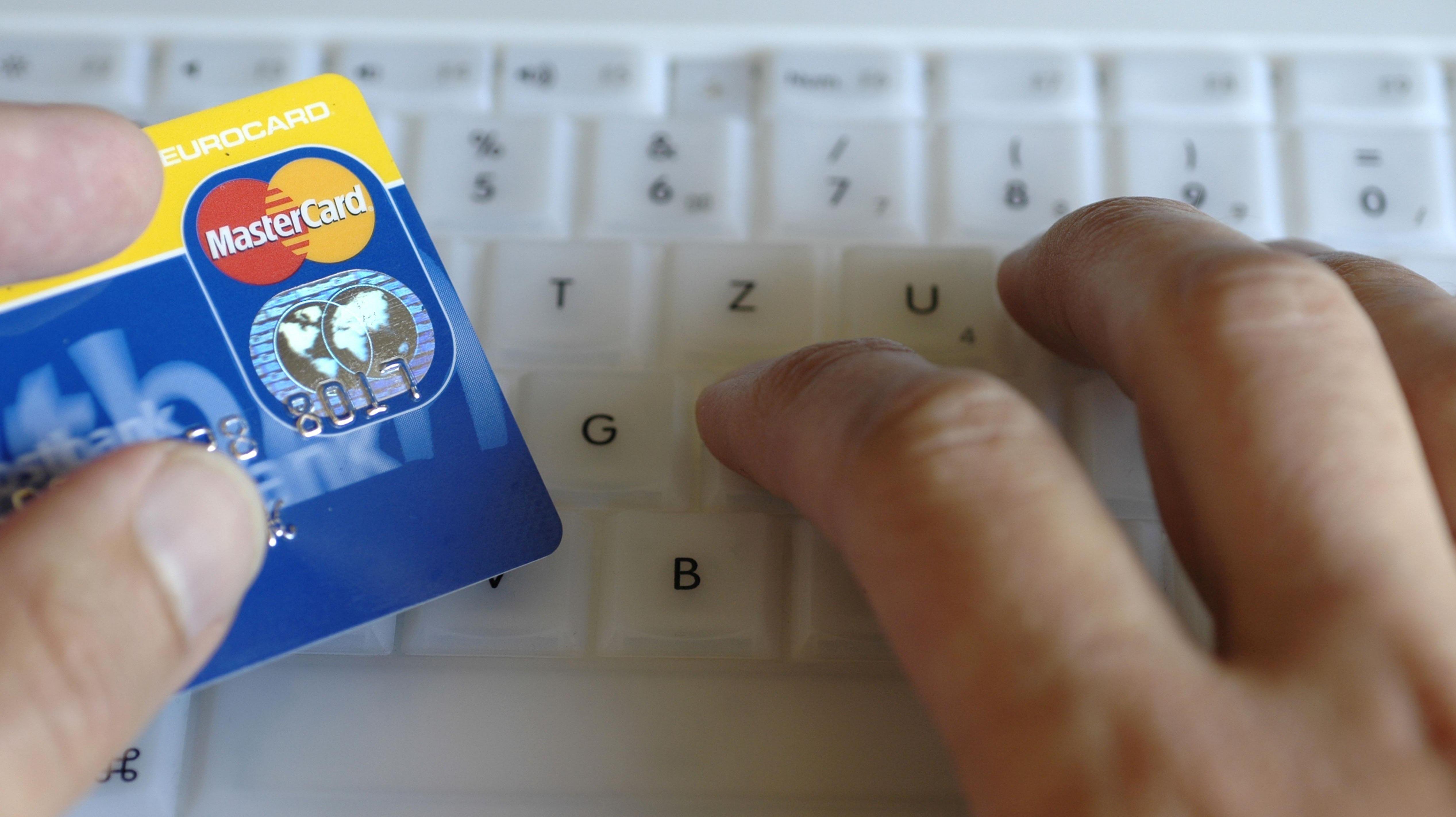 Mann arbeitet am Computer mit Kreditkarte in der Hand