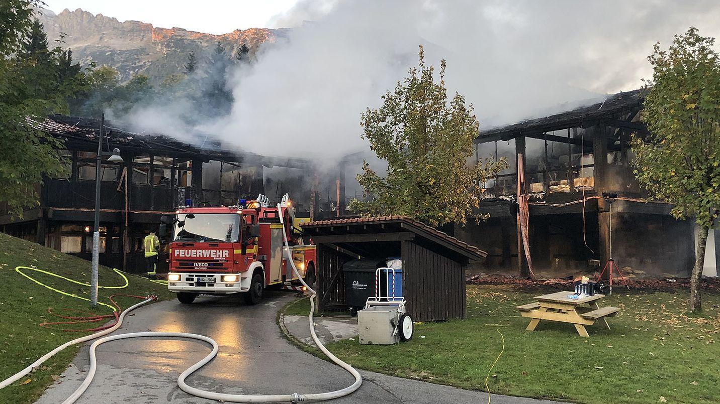 Feuerwehr mit Löschschlauch vor abgebranntem Schulgebäude