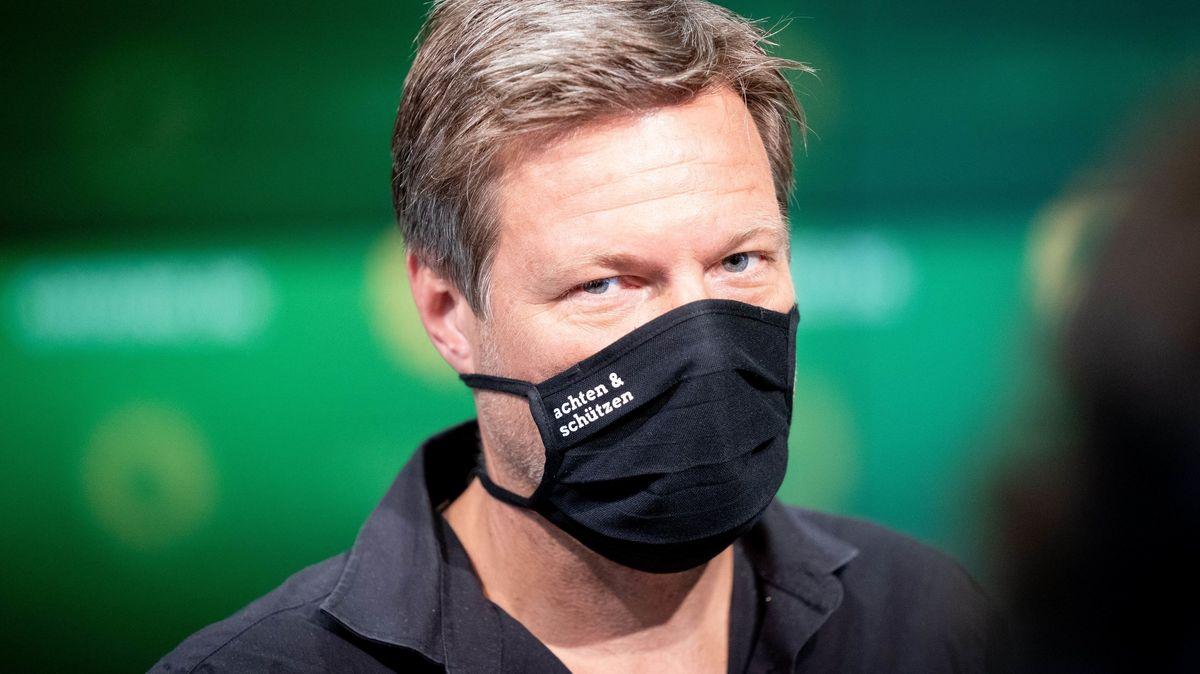 """Grünen-Parteichef Robert Habeck mit schwarzem Mundschutz auf dem """"achten & schützen"""" steht"""